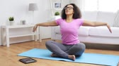 гаджет : fitness, sport, yoga, training and people concept - happy african woman in lotus pose exercising on mat at home Стоковые видеозаписи