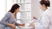 fertilidade : pregnancy, gynecology, medicine, health care and people concept - gynecologist doctor with clipboard and pregnant woman meeting at hospital Stock Footage