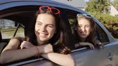 vacation : summer vacation, holidays, travel, road trip and people concept - happy teenage girls or young women in car at seaside