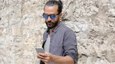 muro de pedras : leisure, technology, communication and people concept - smiling man in sunglasses texting message on smartphone at stone wall