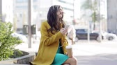 гаджет : technology, lifestyle and people concept - smiling young woman or teenage girl with smartphone and headphones listening to music and drinking coffee on city street