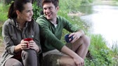 margem do rio : travel, tourism, hike, camping and people concept - happy couple with cups drinking in nature