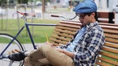 fixní : lifestyle, creativity, art, inspiration and people concept - creative man or artist with pencil and sketchbook drawing something sitting on city street bench over fixed gear bicycle