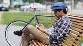 hat : lifestyle, creativity, art, inspiration and people concept - creative man or artist with pencil and sketchbook erasing his drawing sitting on city street bench over fixed gear bicycle Stock Footage