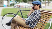 hat : leisure, technology, communication and people concept - smiling man calling on smartphone sitting on city street bench with coffee cup over fixed gear bicycle