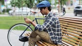велосипед : leisure, technology, communication and people concept - creative man with tablet pc computer sitting on city street bench over fixed gear bicycle Стоковые видеозаписи
