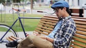 style : lifestyle, creativity, art, inspiration and people concept - creative man or artist with pencil and sketchbook drawing something sitting on city street bench over fixed gear bicycle