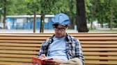 escritor : lifestyle, creativity, freelance, inspiration and people concept - creative man with notebook or diary writing sitting on city street bench Vídeos