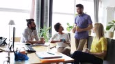 şirket : business, communication and people concept -happy creative team drinking coffee at break and having discussion in office Stok Video