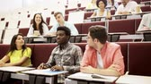 salão : education, high school, university, learning and people concept - group of international students with notebooks sitting in lecture hall and talking