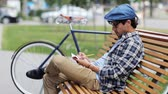 fixní : lifestyle, creativity, freelance, inspiration and people concept - creative man with pencil writing to notebook or diary sitting on city street bench over fixed gear bicycle
