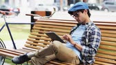 fixní : leisure, technology, communication and people concept - creative man with tablet pc computer sitting on city street bench over fixed gear bicycle Dostupné videozáznamy