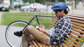 fixní : lifestyle, creativity, art, inspiration and people concept - creative man or artist with pencil and sketchbook erasing his drawing sitting on city street bench over fixed gear bicycle Dostupné videozáznamy