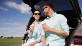 auto : travel, summer vacation, road trip, leisure and people concept - happy couple drinking coffee from disposable cups sitting on trunk of hatchback car outdoors and talking