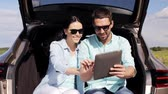 гаджет : technology, travel, vacation, road trip and people concept - happy couple with tablet pc computer sitting on trunk of hatchback car outdoors and searching location or destination