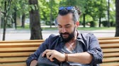 barba : travel, tourism, lifestyle and people concept - man with earphones and sunglasses sitting on city bench and looking for something in his backpack