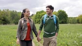путешествие : travel, hiking, backpacking, tourism and people concept - happy couple with backpacks holding hands and walking outdoors Стоковые видеозаписи