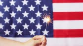american independence day, patriotism, holidays and people concept - close up of hand holding sparkler over national flag Stok Video