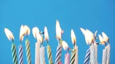 celebrar : holiday, celebration and party concept - birthday candles burning over blue background and extinguished