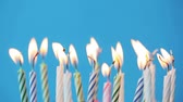огонь : holiday, celebration and party concept - birthday candles burning over blue background Стоковые видеозаписи