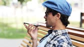 hat : leisure, technology, communication and people concept - man calling and talking by smartphone speakerphone on city street Stock Footage