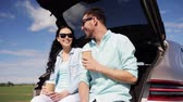 předměstský : travel, summer vacation, road trip, leisure and people concept - happy couple drinking coffee from disposable cups sitting on trunk of hatchback car outdoors and talking