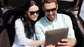 finding : technology, travel, vacation, road trip and people concept - happy couple with tablet pc computer sitting on trunk of hatchback car outdoors and searching location or destination