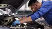 motor : car service, repair, maintenance and people concept - mechanic man with wrench and lamp working at workshop
