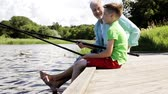 pesca : grandfather and grandson fishing on river berth 13 Stock Footage