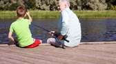 vnuk : grandfather and grandson fishing on river berth 18
