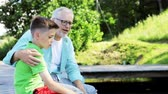 parente : grandfather and grandson sitting on river berth 26 Stock Footage