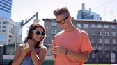 showing : happy teenage couple with smartphones in city Stock Footage
