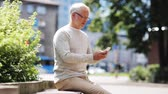 mais velho : senior man texting message on smartphone in city