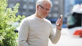 mais velho : senior man calling on smartphone in city