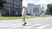 downtown : senior man walking along city crosswalk