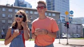 augmented reality : happy teenage couple with smartphones in city Stock Footage