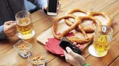 alemão : male friends with smartphones drinking beer at bar