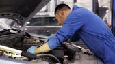 mechanic man with wrench repairing car at workshop 8 Stock Footage