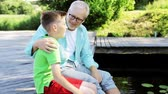 parente : grandfather and grandson sitting on river berth