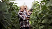 call : old woman calling on smartphone in farm greenhouse