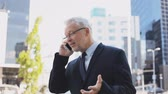 evil : senior businessman calling on smartphone in city Stock Footage