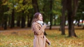 comando : woman with smartphone walking in autumn park Stock Footage