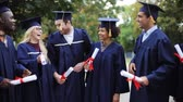 roucho : happy students in mortar boards with diplomas