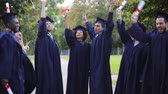 jumping : happy students in mortar boards with diplomas