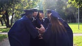 university : happy students in mortar boards with hands on top