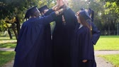 graduating : happy students in mortar boards making high five Stock Footage