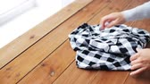 lavanderia : woman folding checkered shirt on table at home