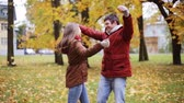 смех : happy young couple throwing autumn leaves in park Стоковые видеозаписи