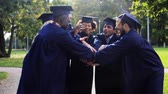 internacional : happy students in mortar boards with hands on top