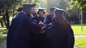 celebrando : happy students in mortar boards with hands on top